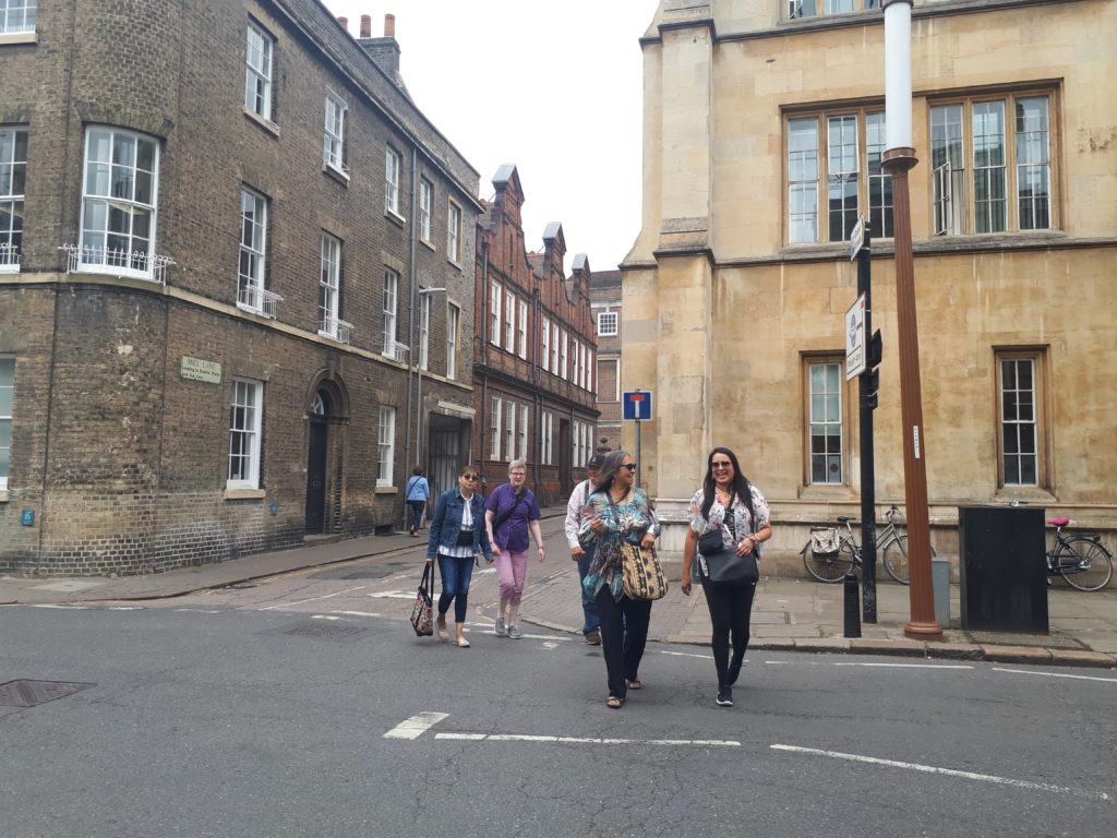 Velma Potts, Josephine Mills, Jerry Potts, Carol Murray, and Melissa Shouting walk towards the Museum of Anthropology and Archeology in Cambridge, UK.
